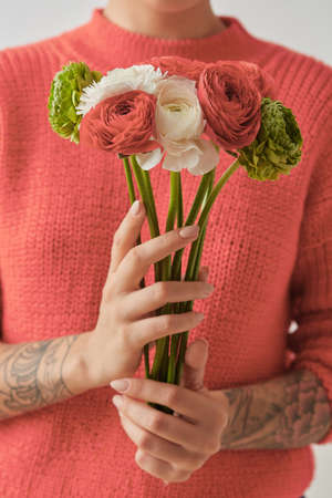 Young girl in a sweater in a color of the year 2019 Living Coral Pantone holding a bouquet of fresh flowers in her hands with tatoo.