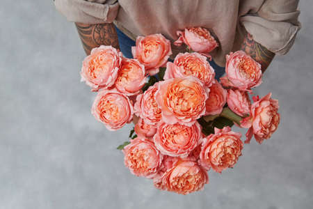 Beautiful bouquet of fresh roses in womans hands with tatoo in a color of the year 2019 Living Coral Pantone on a gray background with copy space. Top view. Archivio Fotografico