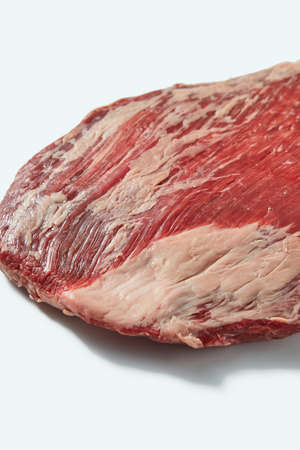 Fresh organic natural raw flank steak, close up structure ob beef on a white background, copy space.