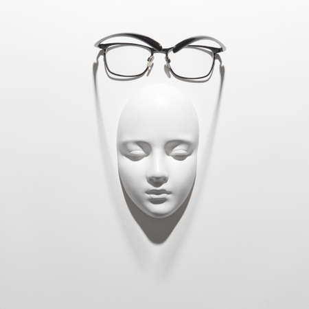 Plaster face mask with elegant glasses above it on a white background with soft long shadows, copy space. Flat lay. 写真素材