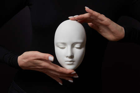 Two womans hands hold white gypsum mask face on a black background. Concept social psychological masks