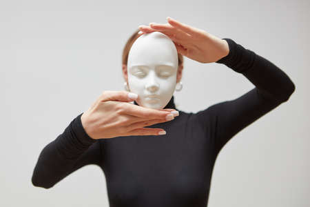 Womans hands hold gypsum mask. Girl in a black jumper with plaster sculpture on a white background. Concept The masks we wear.