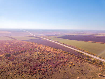 Panoramic landscape with endless farmlands, forests and highway in a autumn time on a background of clear sky. Aerial view from drone.