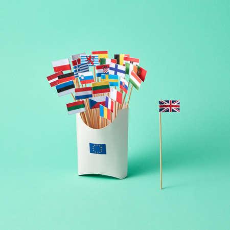 Bandera de papel de Gran Bretaña y una caja de cartón con un signo de la UE y diferentes banderas sobre un fondo verde con espacio de copia. La salida de Gran Bretaña de la UE