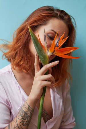 Sexy woman with tattoo holding a strelitzia flower in her hands on a blue background with copy space. Valentines day card 版權商用圖片