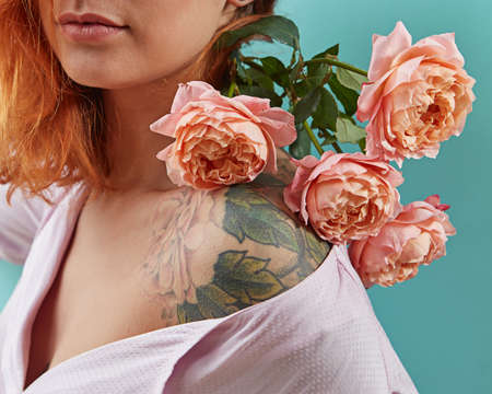 Young cute girl with tattoo on her shoulders and a bouquet of coral roses on a blue background. Postcard to Mothers day. Standard-Bild