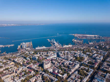 Aerial view of the drone on the city of Odessa and the sea with a maritime station against a blue sky on a sunny day