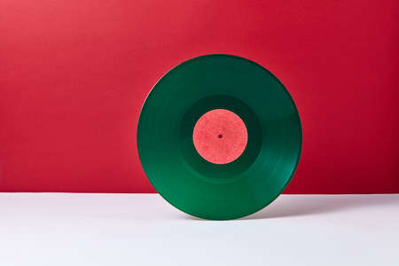 A round music green vinyl record on a duotone red gray background. Retro audio technology. Place for text.