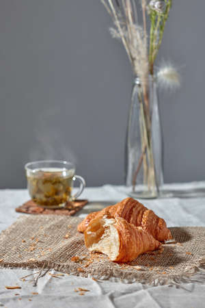 Delicious morning breakfast setting with french homemade pastry, cup of green aromatic fresh tea and flower's vase on a grey textile background. Place for text.