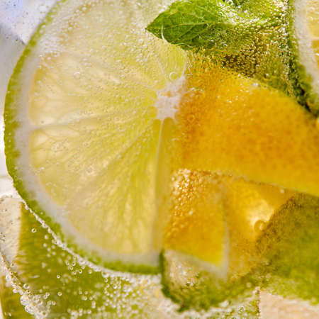 Glass with a cold refreshing homemade lemonade with pieces of lime, lemon, mint leaves and aerated gassed bubbles. Macro summer drink background.