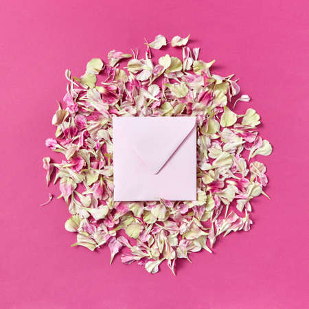 Mockup handmade envelope on a round frame from petals on a magenta background. 스톡 콘텐츠