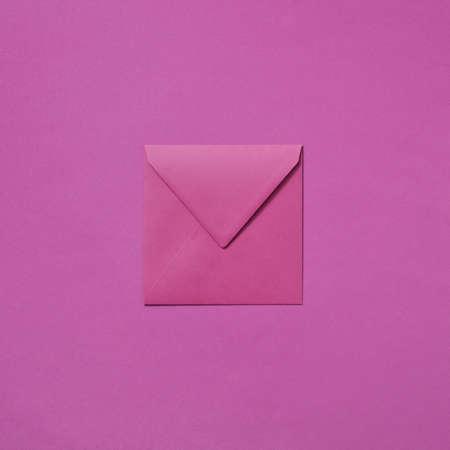 Craft envelope mock-up for invitation on a magenta background.