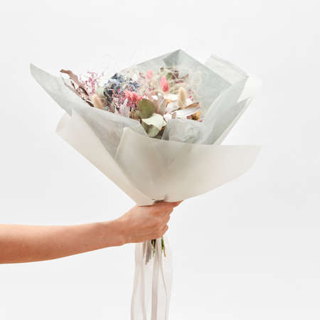 Greeting bouquet from flowers in a hand on a light backhround. 스톡 콘텐츠