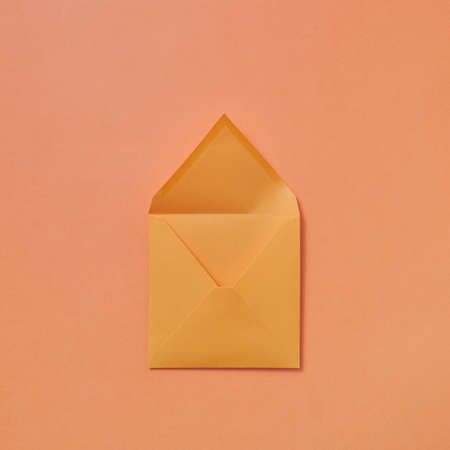 Handmade blank mock-up envelope on a peach color background. 스톡 콘텐츠