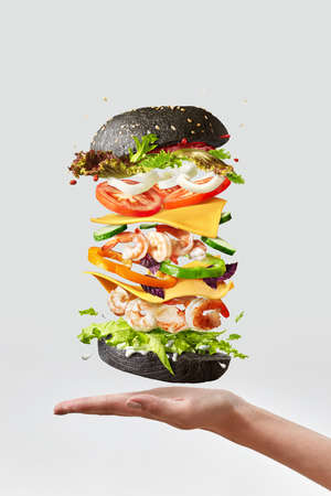 Healthy homemade burger with fresh shrimp and vegetables above the hand on a light background.
