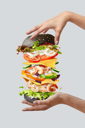 Flying burger with fresh ingredients between womans hands on a light background.
