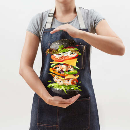Woman holds a flying homemade burger from fresh organic ingredients on a light background.