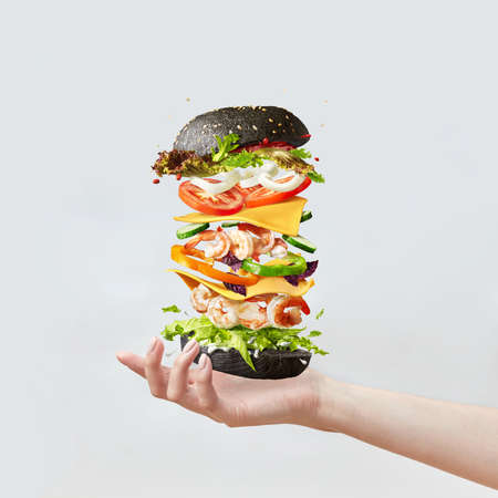 Womans hand holds healthy sandwich from fresh seafood and vegetables on a light background.
