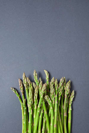Heap of fresh natural asparagus on a gray background. 스톡 콘텐츠