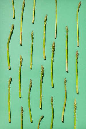 Fresh organic asparagus pattern on a pastel green background. 스톡 콘텐츠