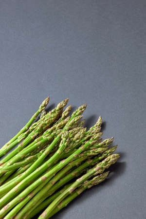 Pile of green organic asparagus on a grey background.