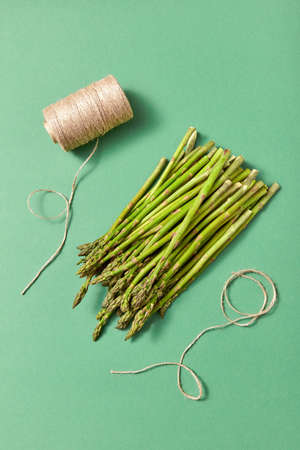 Bunch of natural healthy asparagus and a coil of rope on a green background.