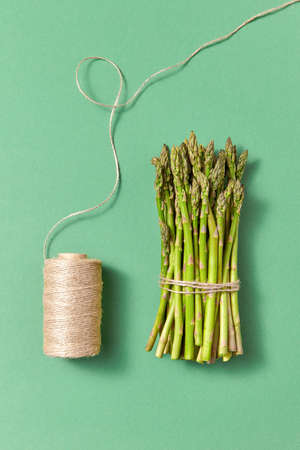 Organic natural asparagus in a bundle and coil of rope on a green background.