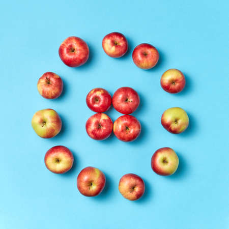 Round apples frame on a blue background.