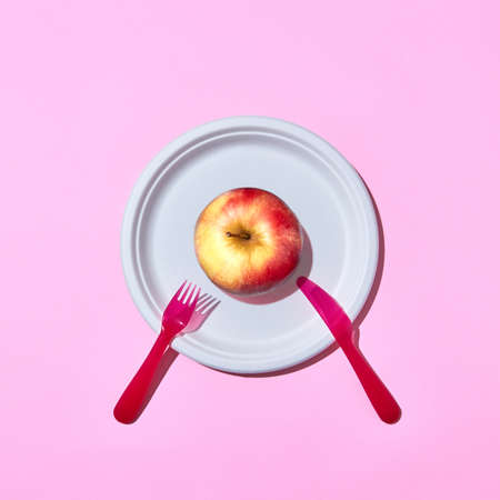 Fresh apple on a plate served with plastic knife and fork