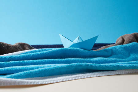 Seascape made from terry towels with paper boat and rocks.