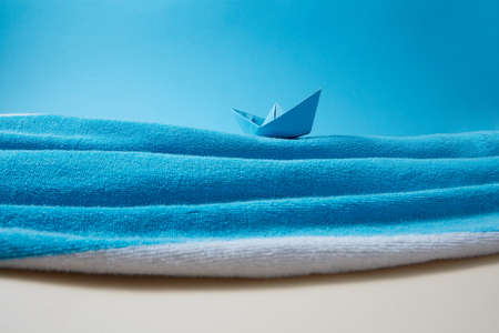 Waves of blue sea made from beach towel with paper boat.