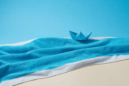 Paper boat on a terry blue towel as a seascape. 스톡 콘텐츠