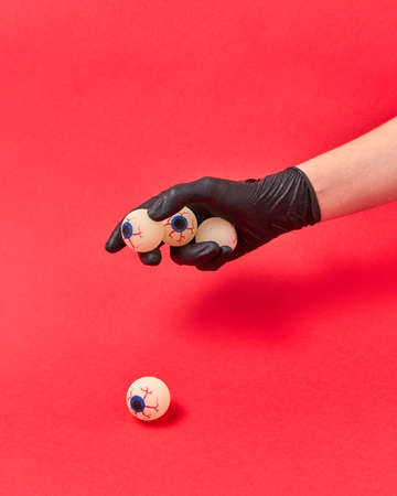 Woman hand in a black glove holds human eyeballs on a red background, copy space. Halloween simbol.