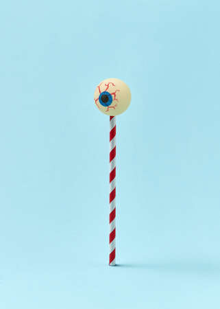 Halloween treat human eyeball on a plastic stick as a lollypop, sweet candy dessert on a light blue background, copy space.