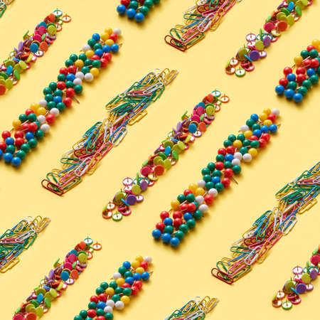 Diagonal multicolored collection of stationery strips paperclips and pins on an yellow background with copy space. Back to school concept.