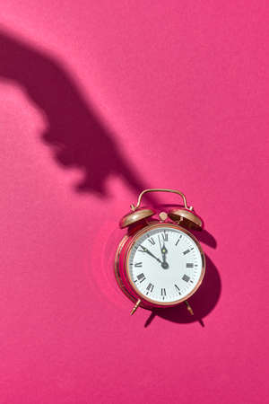 Hard shadow from female's hand presses on old-fashioned cooper painted alarm clock on a hot pink background with copy space.