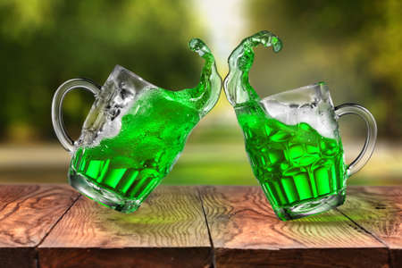 Two flying beer mugs with green alcoholic fresh drink splash on a wooden table against natural blurred background, copy space. Happy St.Patrick 's Day concept.