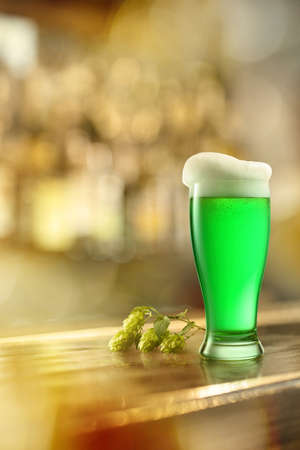 Glass of cold fresh green beer and branch of green hop on a wooden bar counter in pub with free space for your text. Happy St.Patrick s Day concept. Reklamní fotografie
