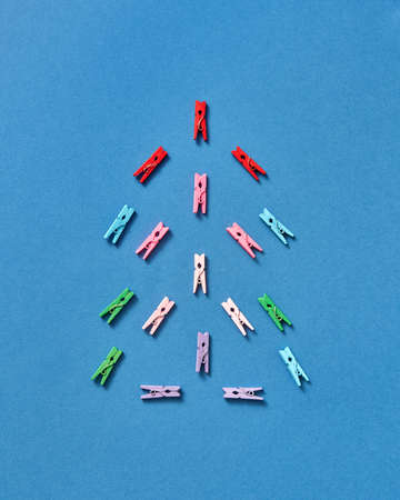 Multicolored clothespegs in the shape of christmas tree on a blue background with copy space. Top view.
