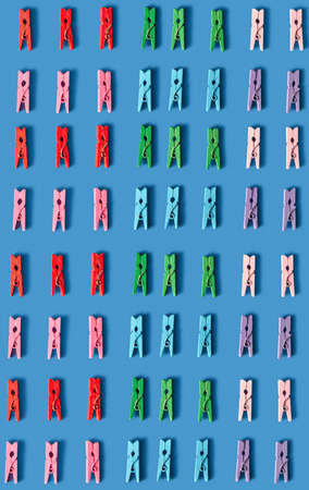 Multicolored vertical plastic clothespegs laundry pattern on a blue background. Top view.