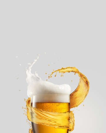 A glass of cold fresh beer with thick white foam and splash around it on a gray background, copy space. Alcohol drinks concept. Zdjęcie Seryjne