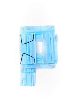 Capital letter P handmade from medical antibacterial protective blue face masks on a white background, copy space. Creative alphabet for making up new words.
