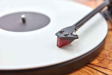Old-fashioned turnable record player on a wooden background.