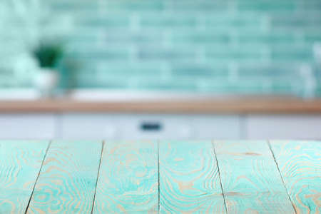 Wooden textured blue table on a background of blurred interior.