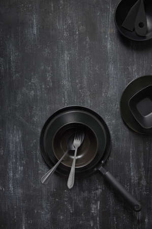 Dinner served table with black cookware on the same color background.