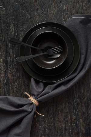 Served kitchen table with cookware and textile napkin in black colors. Banque d'images