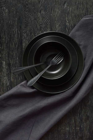 Kitchen table served with black utensils ceramic plates, spoon, fork and textile napkin.