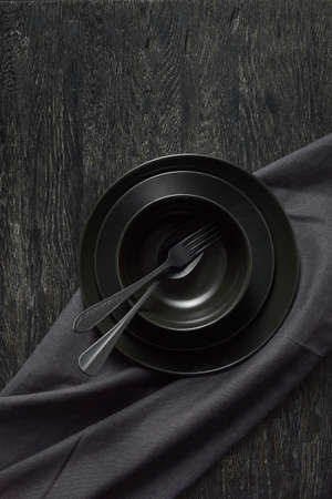 Served kitchen table with black cookware ceramic plates, fork, spoon and textile napkin.