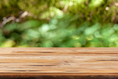 Aged wooden table for montage or display products on a green leaves blurred background. Banque d'images