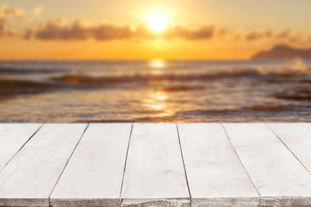 Empty white wooden boards or countertop against seascape with sunset on background. Template, mockup for display or montage of products. Close up Banque d'images